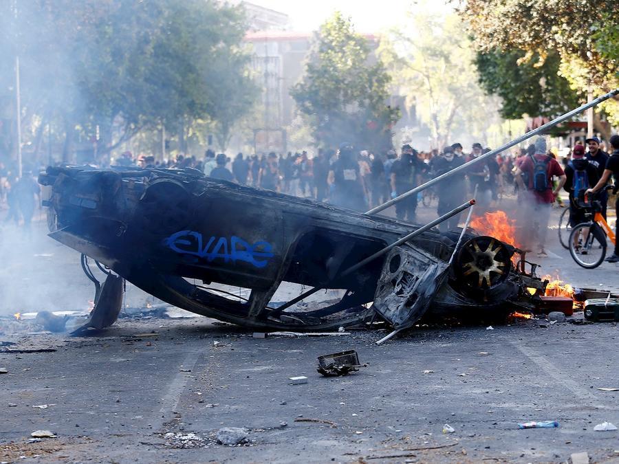 Un carre quemado en una calle de Santiago de Chile, donde este domingo se produjo un nuevo día de graves disturbios.