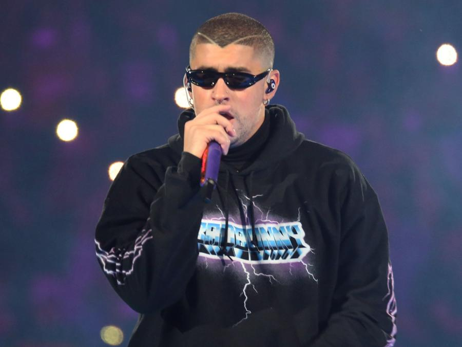 Bad Bunny wearing a hoodie and singing live