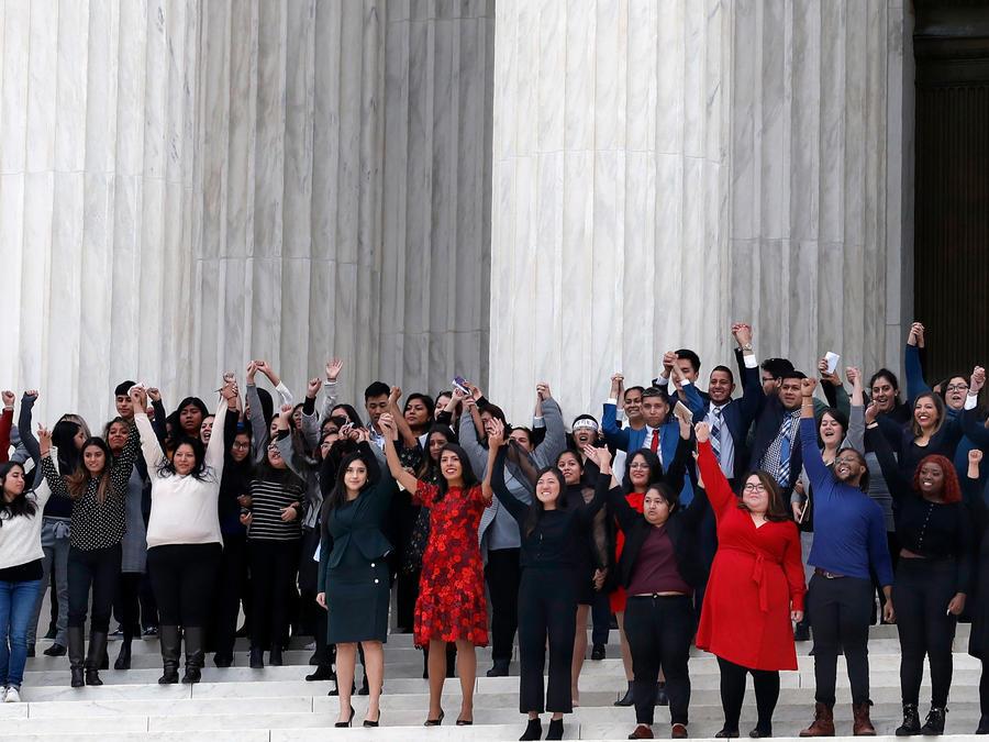 Activistas y beneficiarios de DACA que presentaron este martes argumentos en la Corte Suprema de Estados Unidos a la salida de la sesión con los brazos en alto en señal de victoria