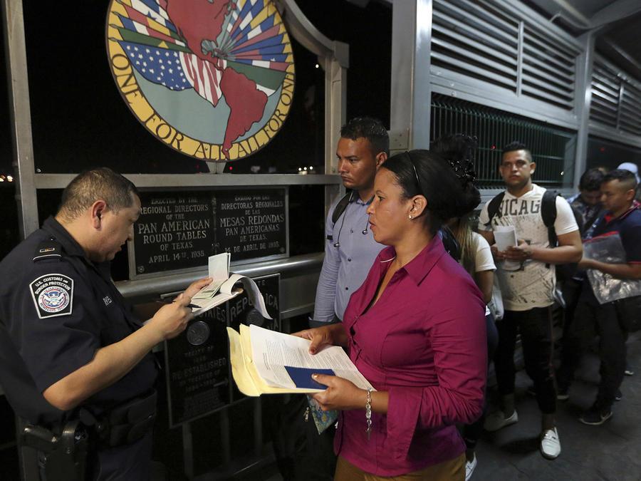 Un oficial del servicio  de Aduanas y Protección de Fronteras revisa los documentos de inmigrantes que buscan asilo.