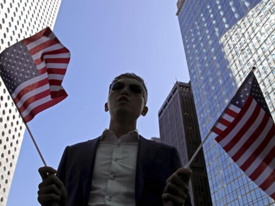Un manifestante antigubernamental de Hongk Kong sostiene en la mano dos banderas de EEUU en el distrito financiero de la ciudad asiática.