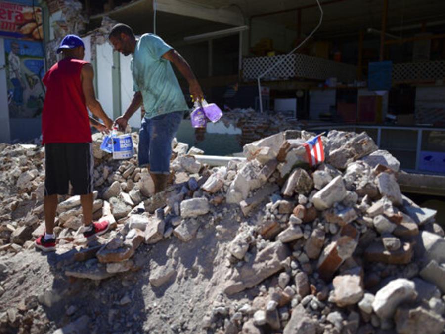 Dos personas sacan productos de una tienda parcialmente colapsada tras un terremoto de 6.4 de magnitud que golpeó Puerto Rico el pasado martes.