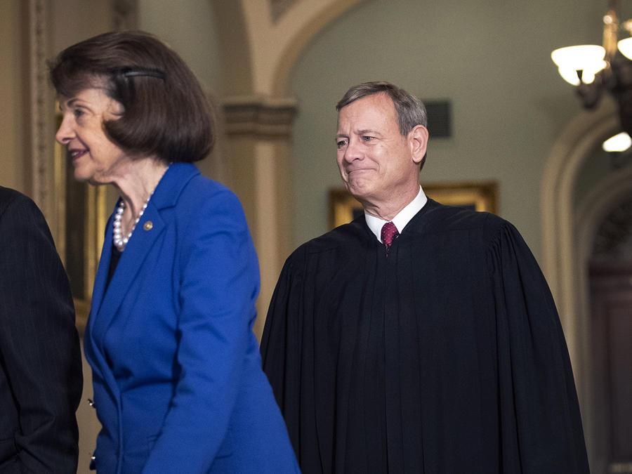 El presidente de la Corte Suprema de Justicia, John Roberts, a la derecha, llega junto a los senadores Roy Blunt y Dianne Feinstein al pleno del Senado para iniciar el juicio político, el 16 de enero en Washington, DC.