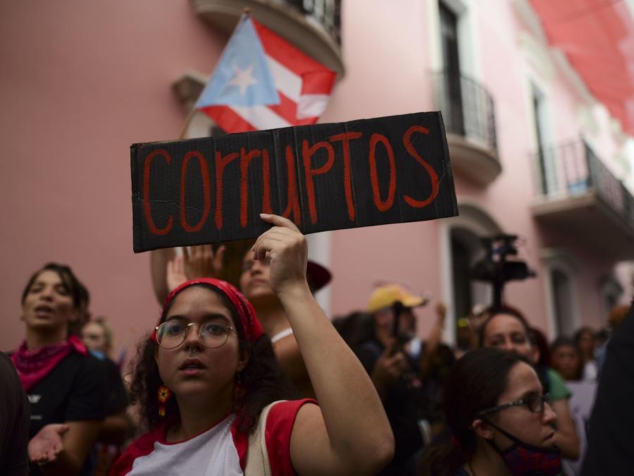Joven sostiene una pancarta durante las protestas contra la gobernadora de Puerto Rico