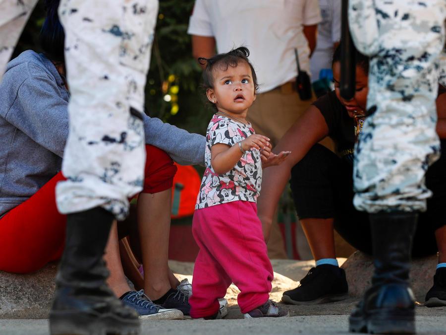 Una niña en la frontera entre México y Estados Unidos junto a su mamá rodeada de agentes.