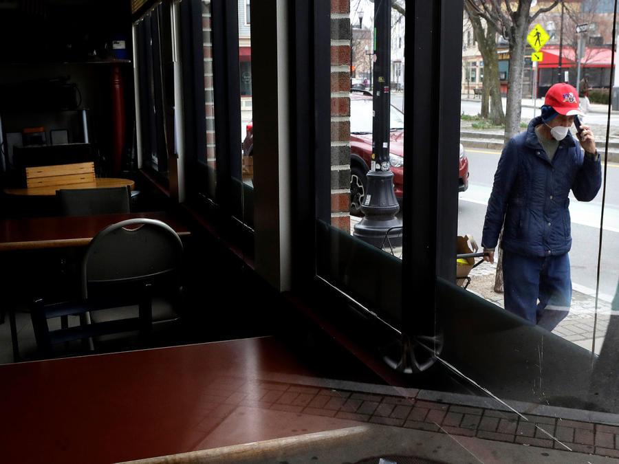 Una persona camina frente a un negocio de comida cerrado debido a la pandemia del coronavirus.