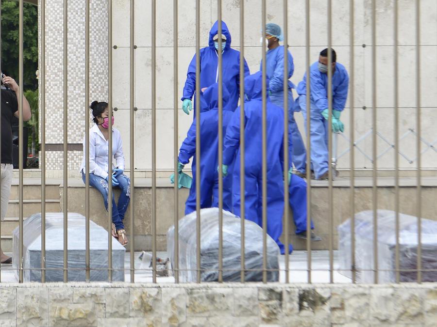 Familiares y personal de un cementerio esperaban para enterrar a presuntas víctimas del nuevo coronavirus en ataúdes envueltos en plástico en Guayaquil, Ecuador, el 1 de abril de 2020.