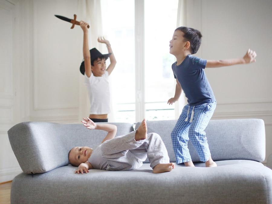Niños jugando en el sillón de la casa