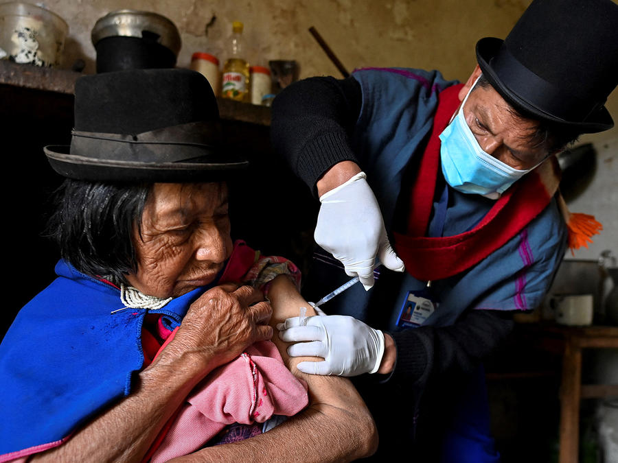 El enfermero indígena de la etnia Misak Anselmo Tunubala, de 49 años, inocula a una anciana indígena con la vacuna Sinovac contra el COVID-19 en el resguardo indígena Guambia, zona rural de Silvia, departamento del Cauca, Colombia, el 15 de abril de 2021.