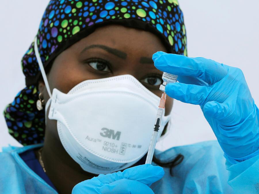 La enfermera registrada Sheba Phillip prepara una jeringa con una dosis de la vacuna Pfizer-BioNTech para el coronavirus, durante un evento de vacunación fuera de la escuela Bronx Writing Academy en el Bronx, Nueva York, 4 de junio de 2021.