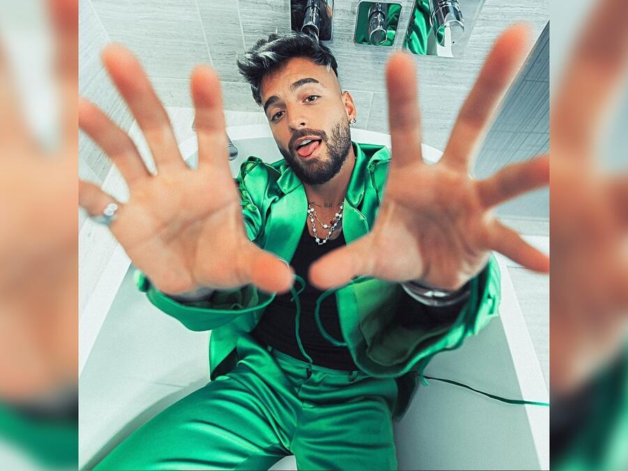 Maluma posando con un look verde