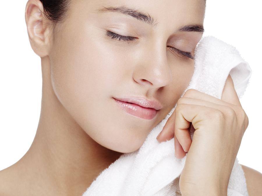 Mujer sosteniendo una toalla junto a su rostro