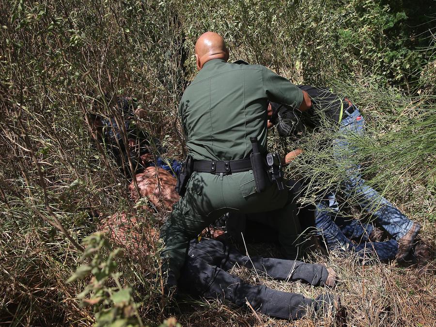 Un agente de la patrulla fronteriza captura a inmigrantes indocumentados que intentaban cruzar la frontera ilegalmente