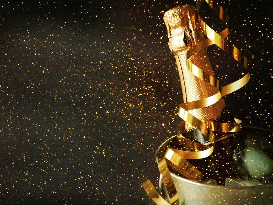 Botella de champaña en una cubeta de hielo con serpentinas doradas