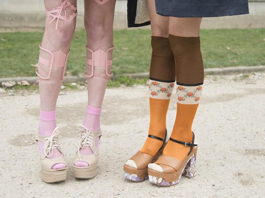 Piernas de dos mujeres con sandalias con calcetines