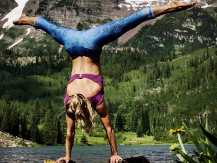 Chelsey Korus haciendo yoga sobre una piedra en el lago