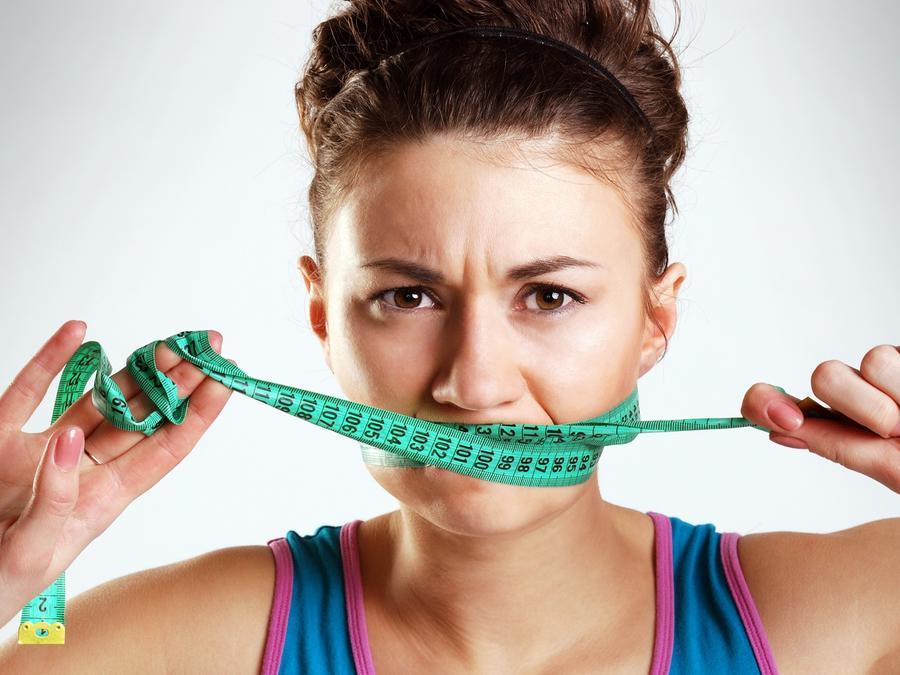 Mujer con blusa azul cubriendo su boca con una cinta de medir