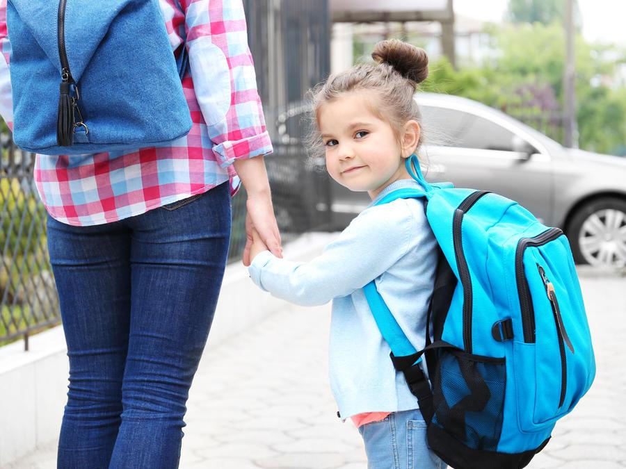 Madre camina con niña hacia la escuela