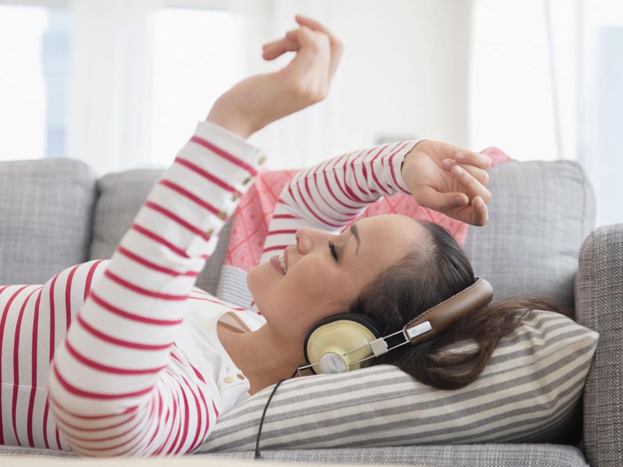 Mujer escuchando música acostada en el sofá