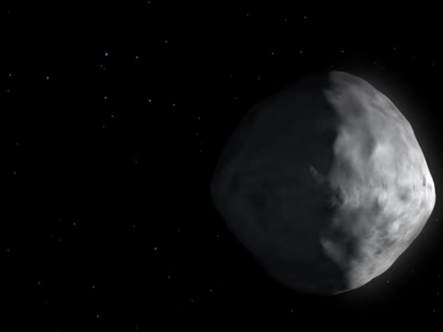 Foto de pantalla de una animación en la que NASA explica cómo luciría el asteroide Bennu al lado de la Tierra