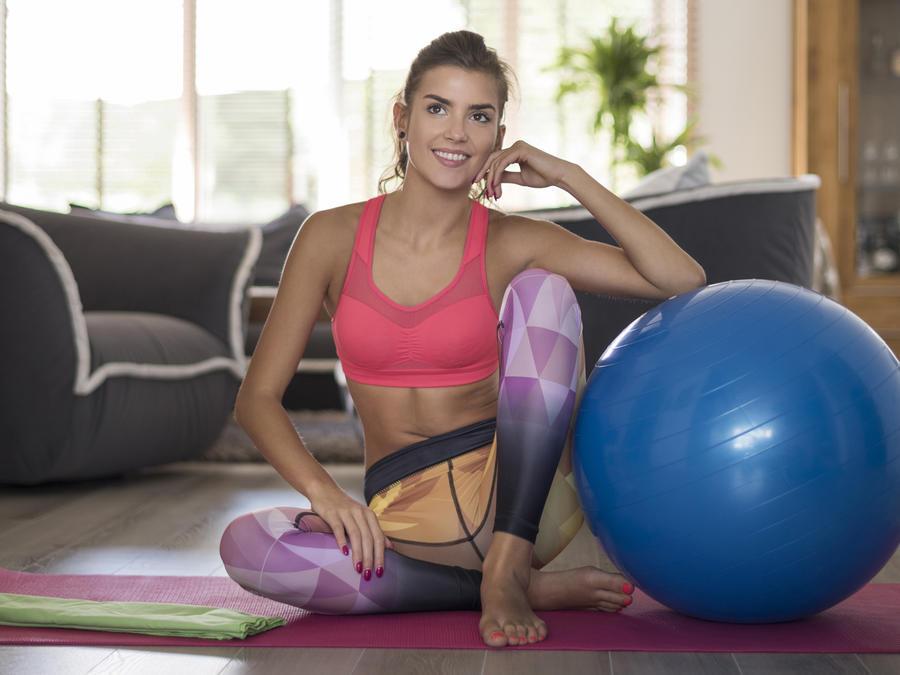 Mujer en ropa deportiva sentada junto a una pelota de ejercicio