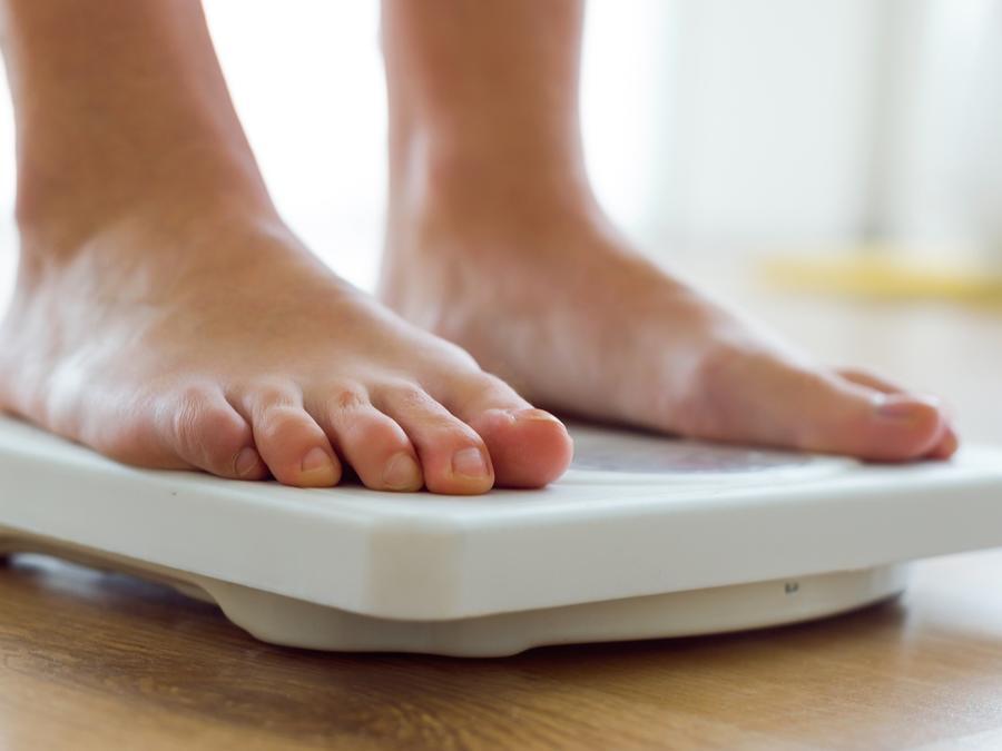 Persona pesándose sobre balanza