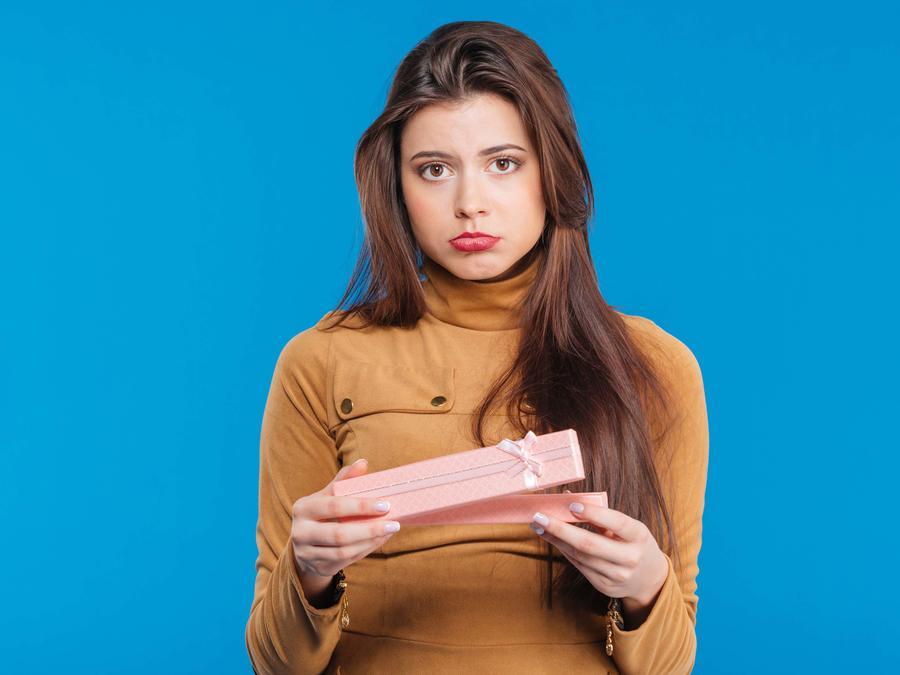Mujer con cara de decepción abriendo un regalo