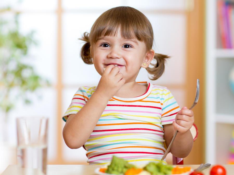 Niña pequeña comiendo vegetales