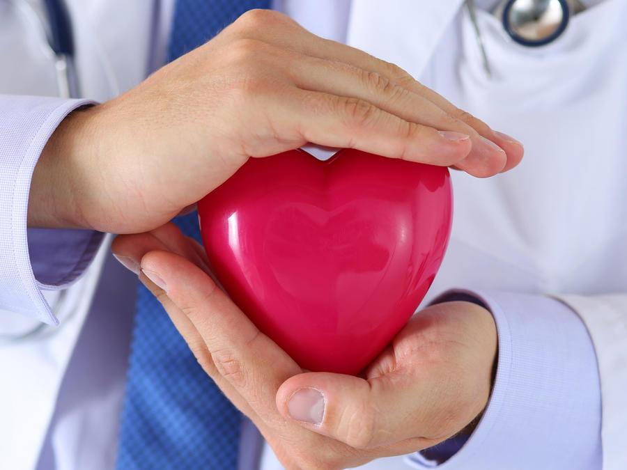 Médico tomando un corazón entre sus manos