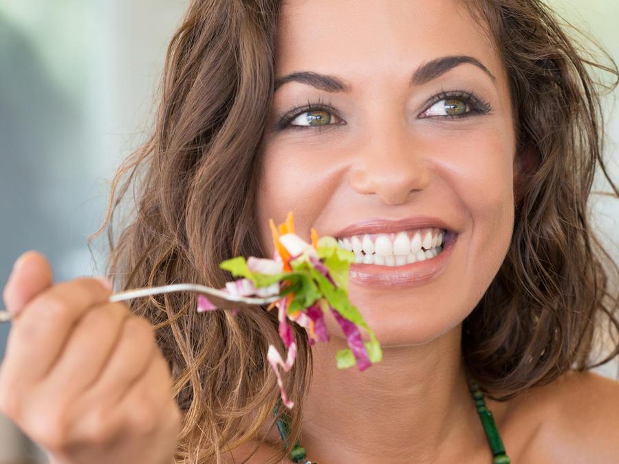Mujer sonriendo comiendo ensalada