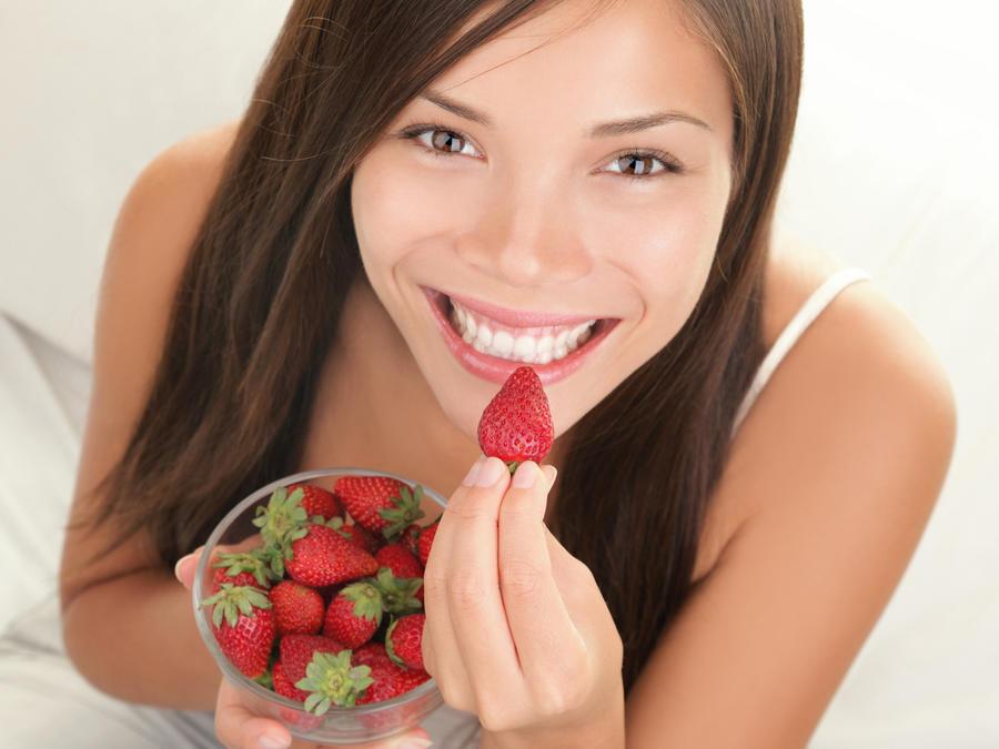 Mujer sonriendo comiendo fresas