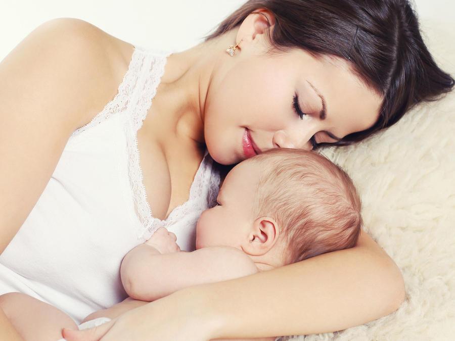 Madre joven durmiendo con su bebé