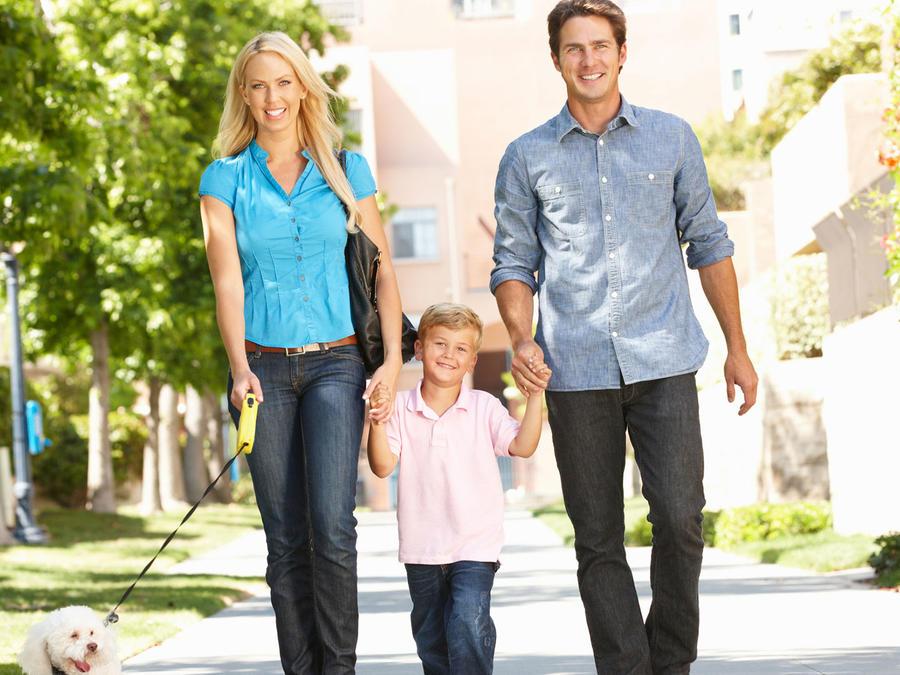 Familia pasea por la calle con su perro