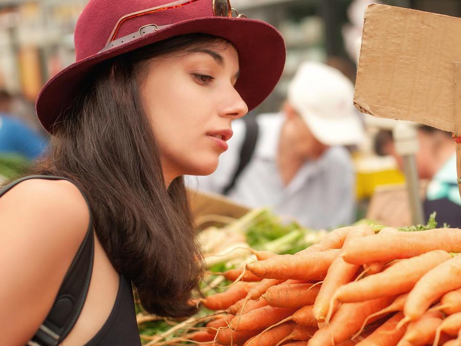 Mujer checa zanahorias en mercado