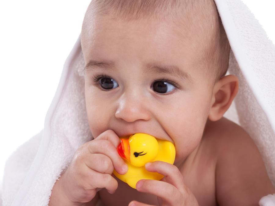 Bebé jugando con patito de hule para el baño