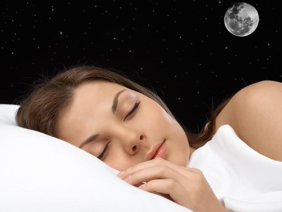 Mujer durmiendo con luna llena en el cielo