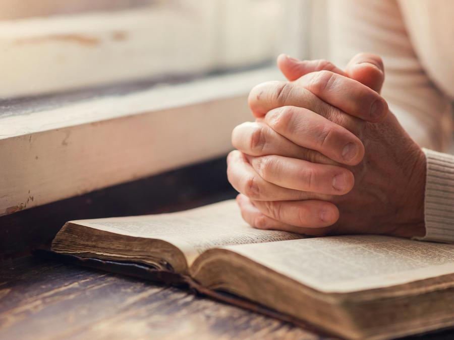 Persona con biblia rezando
