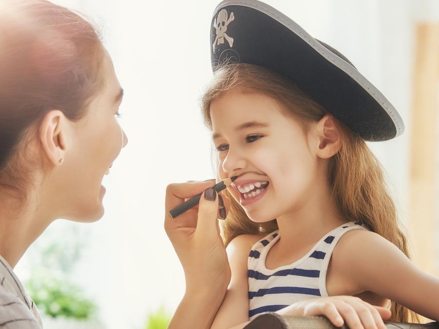 Madre pintando bigote para disfrazar a su hija