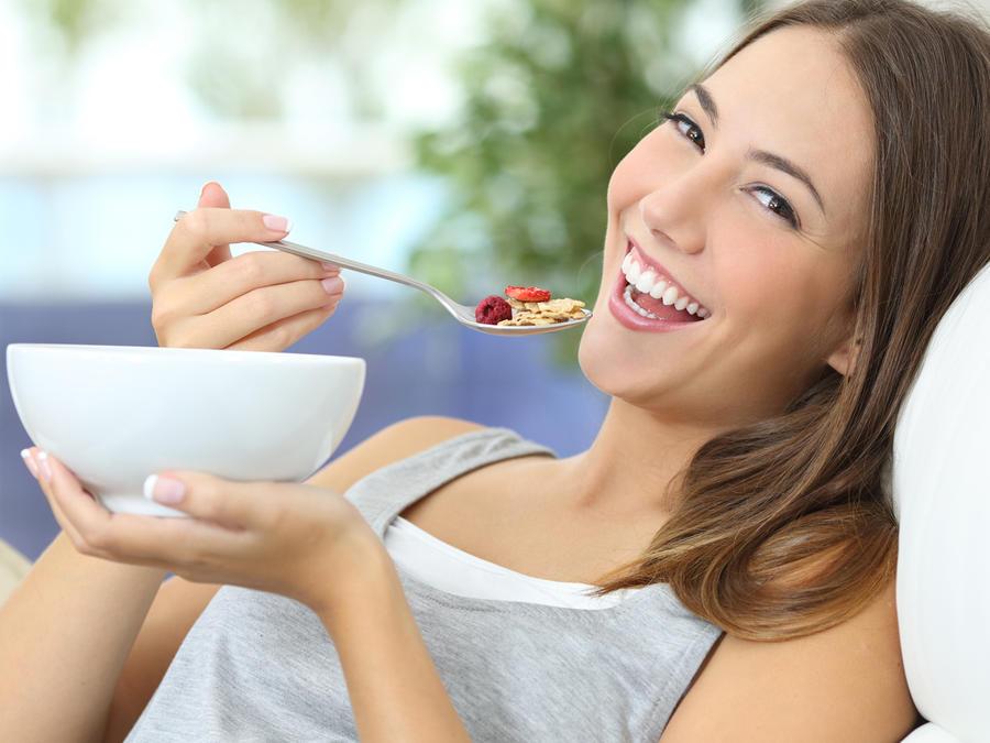 Mujer joven sonriendo mientras come
