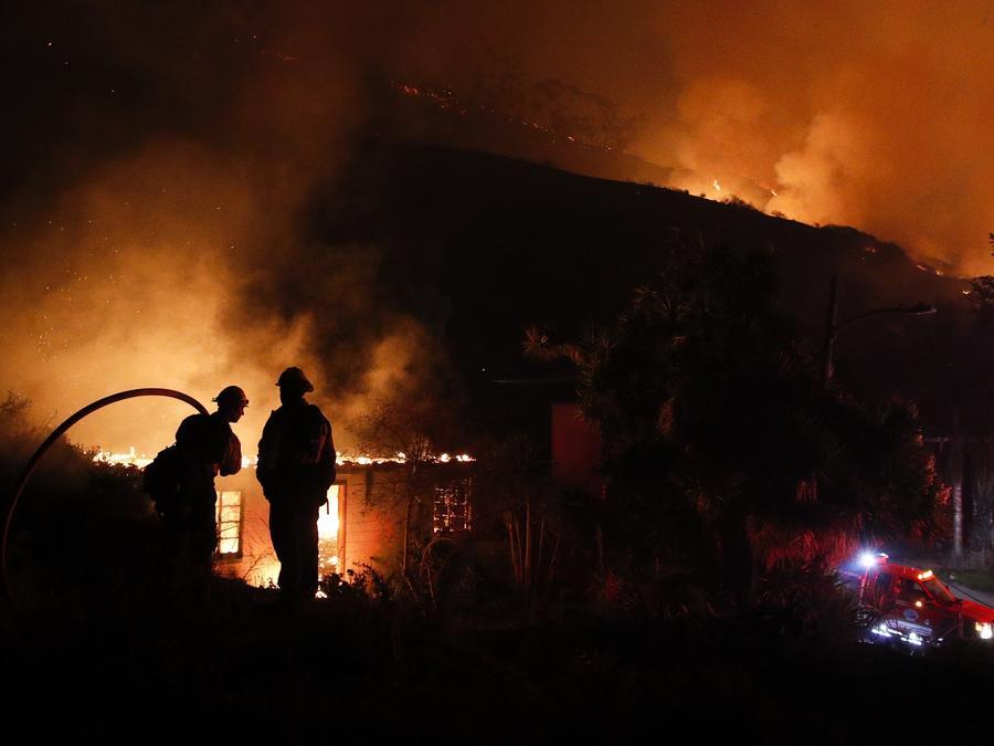 Dos bomberos intentan controlar el fuego que quema una casa en California.