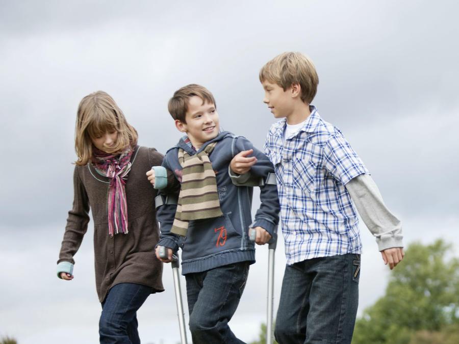 Niños ayudando a otro niño con muleta
