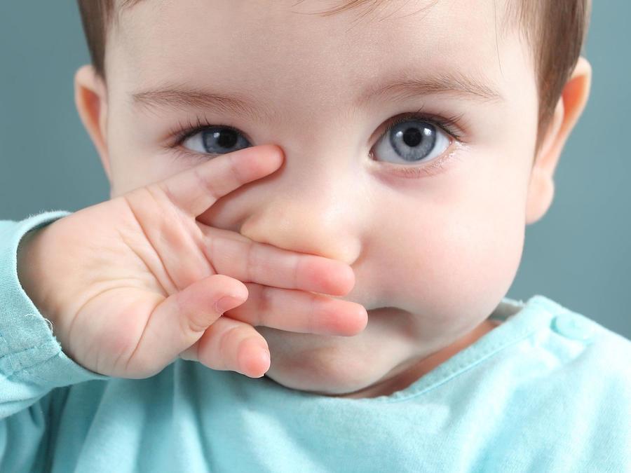 Bebé con la mano en la nariz