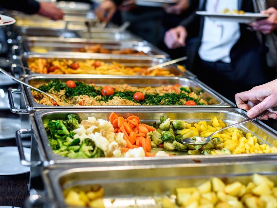 Imagen de archivo de personas sirviéndose alimentosen un comedor.