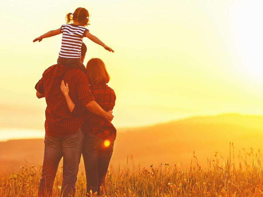 Madre, padre y pequeña hija, al atardecer