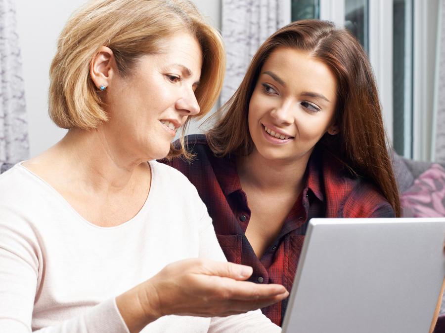 Madre e hija hablando frente a laptop