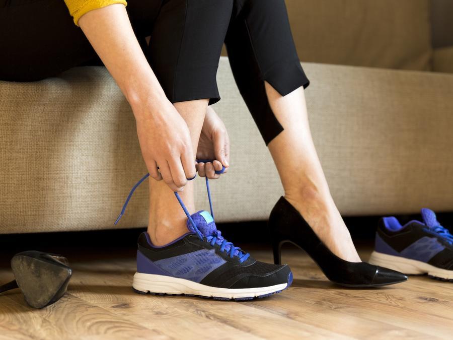 Mujer cambiándose el calzado en sofá