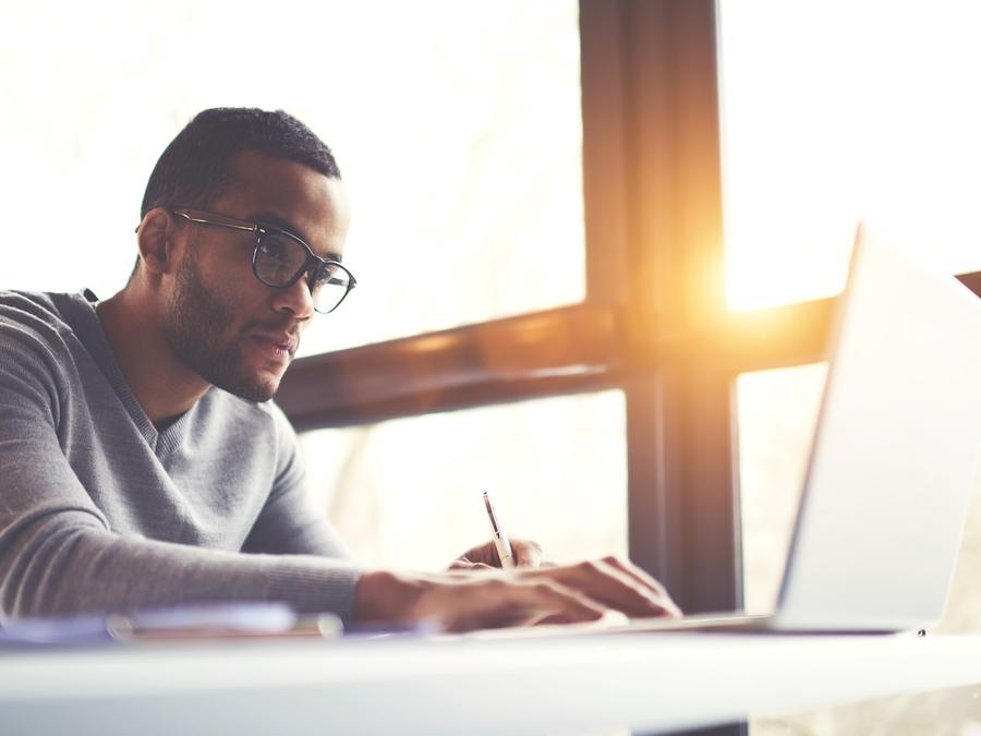 Hombre con anteojos trabajando en computadora