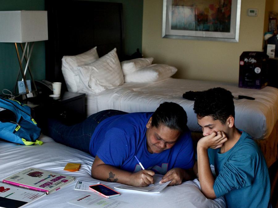 Liz Vázquez ayuda a su hijo Raymond Fernández Vázquez con su tarea en la habitación de un hotel donde viven, en Orlando, Florida, el 6 de diciembre de 2017. Archivo de Alvin Baez / Reuters