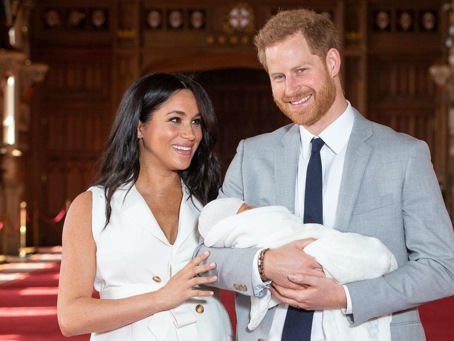 Príncipe Harry con su bebé en brazos y Meghan Markle