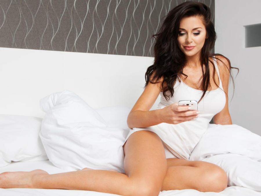 Mujer en la cama observando su celular